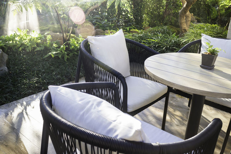 Empty chairs and table in yard during sunny day