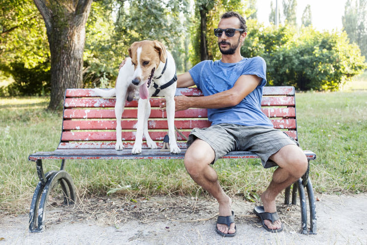 Man with dog sitting on bench in park