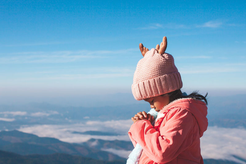 Girl praying while standing against sky during winter