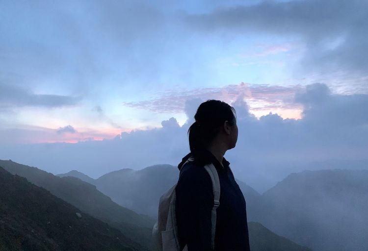 Woman standing against mountains and sky