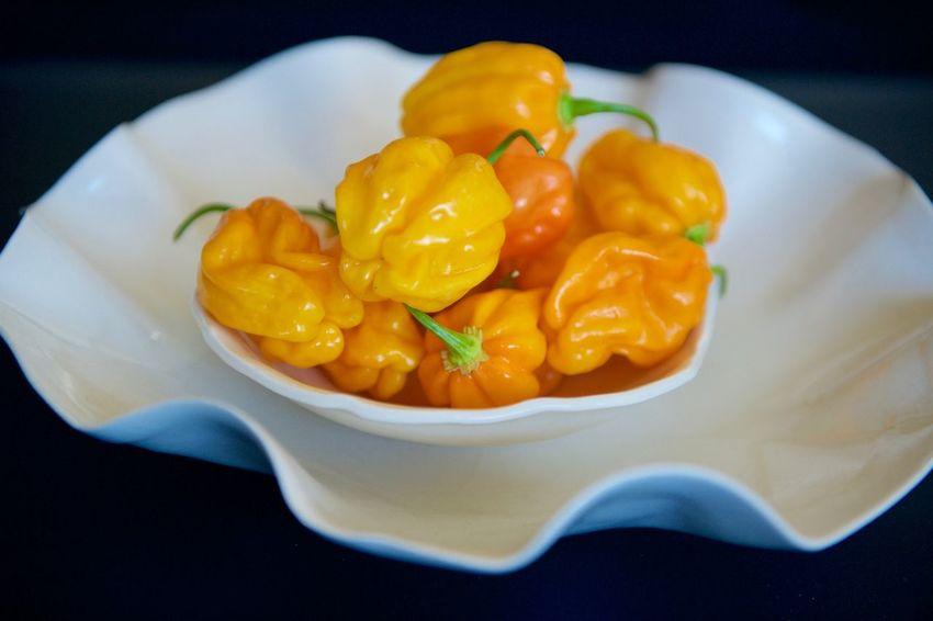 Spicy harbanero peppers on white plates. Close-up Freshness Habanero Peppers Indoors  Orange Pepper Spicy Peppers White Plate Yellow Peppers Yellow Peppers On White Plate