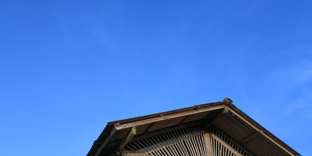 Low angle view of old building against clear blue sky
