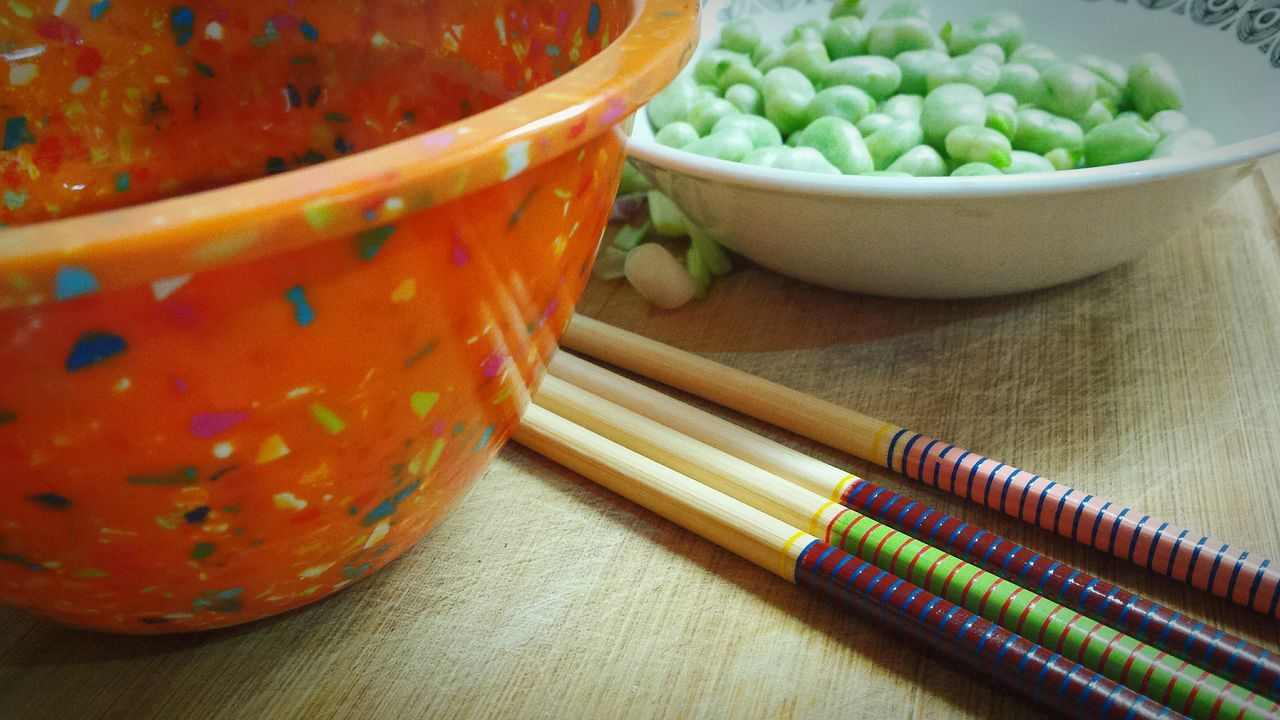 Close-Up Of Bowls Containing Broad Beans With Chopsticks On Table