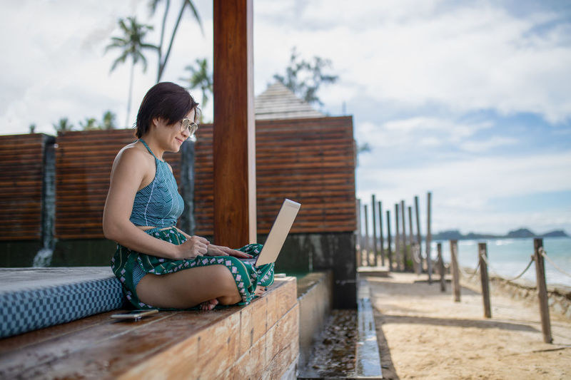 Side View Of Woman Using Laptop While Sitting At Beach