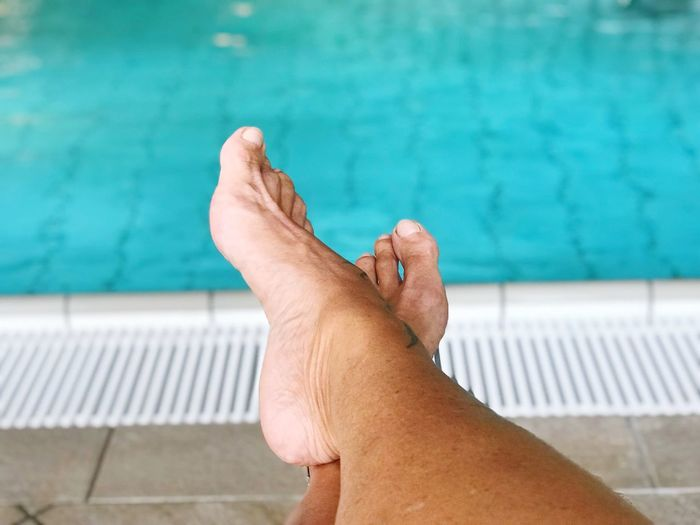 Low section of person against swimming pool