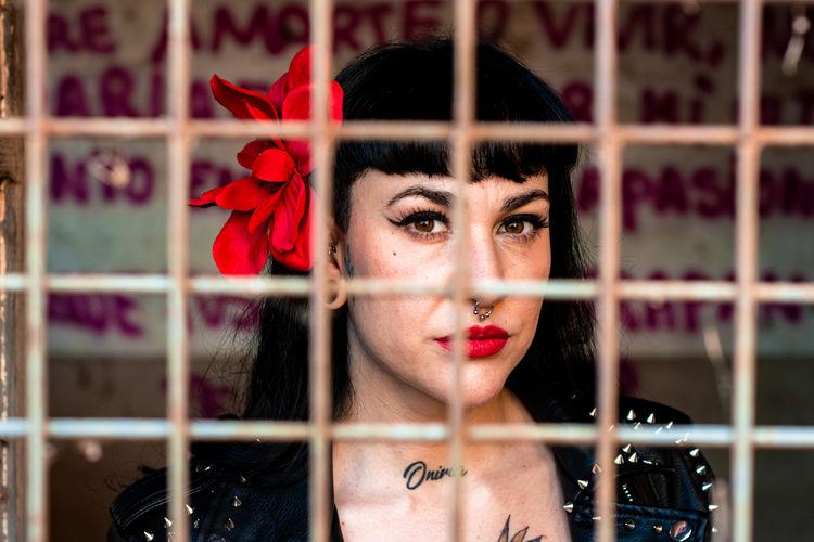 Portrait of woman against metal grate