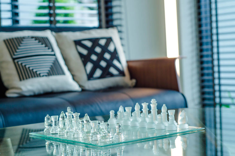 Close-up of chess pieces on board at home