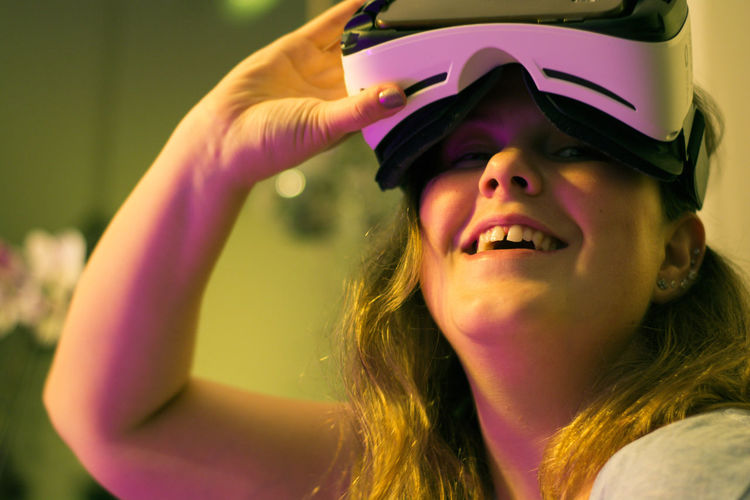 Portrait of happy woman wearing virtual reality simulator in illuminated room