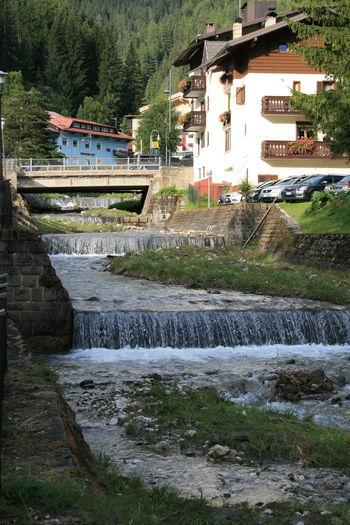 Water splashing on rocks by river against sky