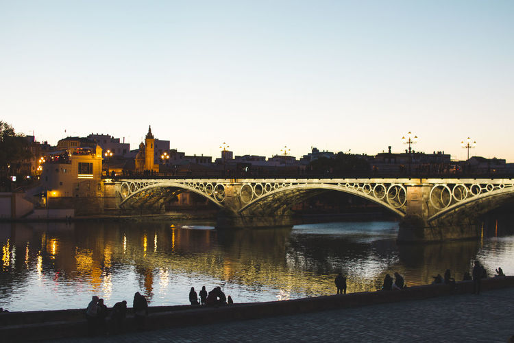 Arch Arch Bridge Architecture Bridge Bridge - Man Made Structure Building Exterior Built Structure City City Life Clear Sky Connection Large Group Of People Leisure Activity Lifestyles Men Real People River Sevilla Silhouette Sky Sunset Togetherness Transportation Travel Destinations Water