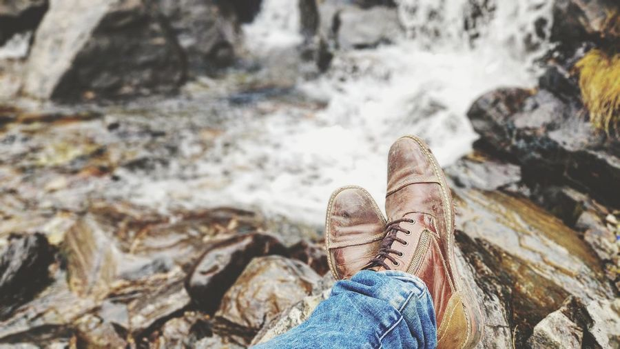 Low section of man wearing shoes on rocks at riverbank