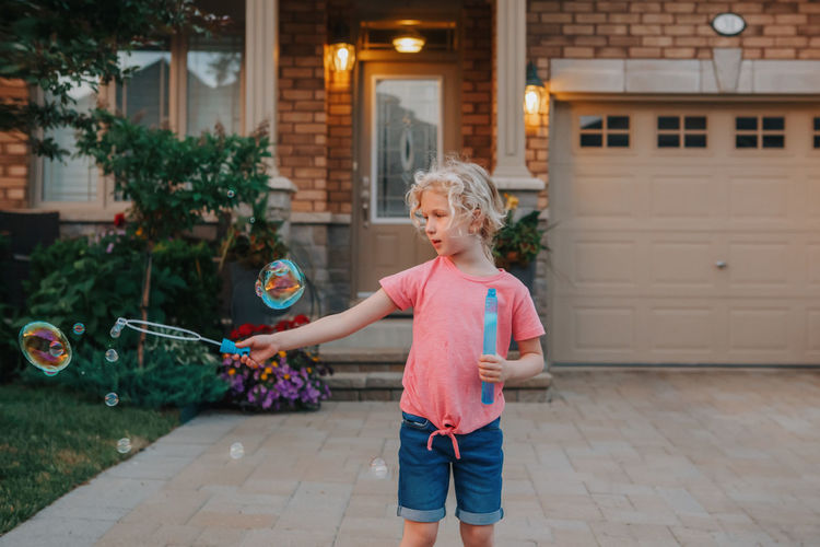 Girl blowing soap bubbles on home front yard. child seasonal summer activity for children.