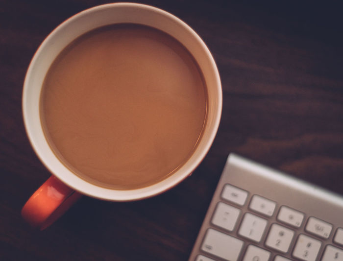 Overhead view of cup of tea next to keypad