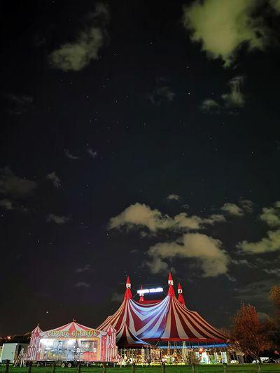 Illuminated amusement park against sky at night