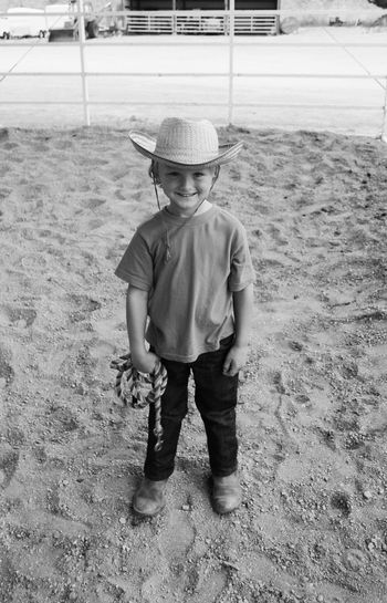 Portrait Of Happy Boy Wearing Cowboy Hat While Standing On Field