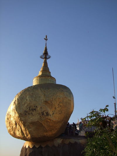 Golden Rock at Mount Kyaiktiyo Pagoda Blue Sky Buddhism Buddhist Culture Buddhist Temple Buddist Temple Clear Sky Composition Golden Rock Golden Rock Pagoda Kinpun Mount Kyaiktiyo Mount Kyaiktiyo Pagoda Myanmar No People Outdoor Photography Pilgrimage Place Of Pilgrimage Place Of Prayer Place Of Worship Religion Rock Sunlight And Shadow Tourism Tourist Attraction  Travel Destinations