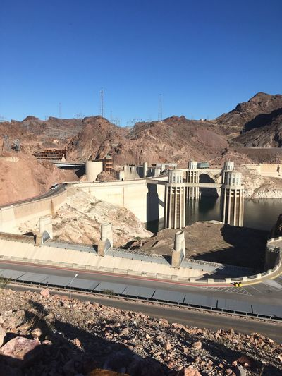 Hoover Dam Mountain Rock - Object Clear Sky Arid Climate Architecture Built Structure No People Hydroelectric Power Fuel And Power Generation Barren Sunlight Desert Sunny Outdoors Dam Shadow Mountain Range Nature Day Blue