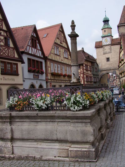 Roden Fountain and Tower Arch Architecture Building Exteriors Cobblestone Composition Facades Flowers Fountain Full Frame Germany Multi Coloured No People Outdoor Photography Plant Quaint  Rothenburg Tourist Attraction  Tourist Destination Tower Town Traditional Buildings Travel Destinations White Clouds
