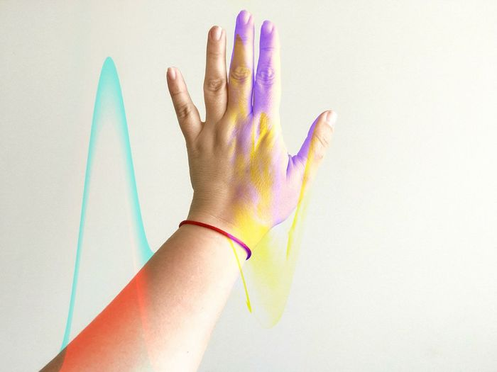 Cropped hand with colorful paints against white background