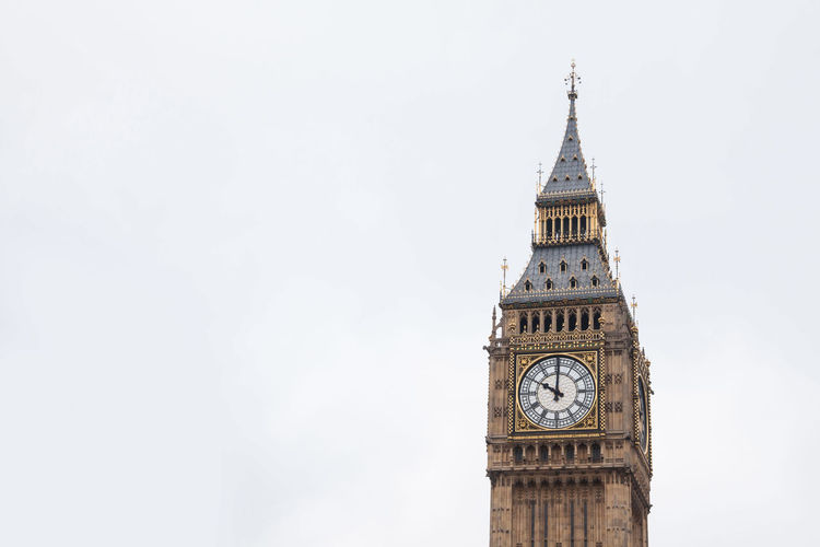 Low angle view of clock tower against sky in city