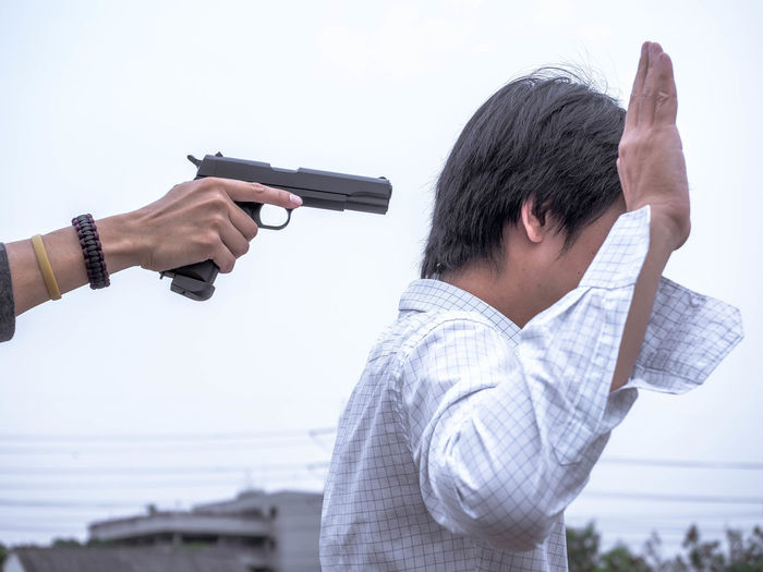 Cropped Hand Aiming Gun On Man With Arm Raised