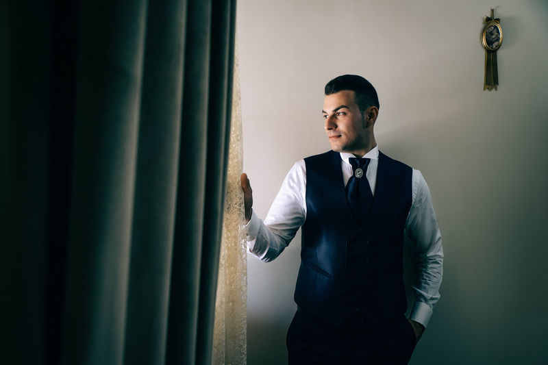 Thoughtful businessman holding curtain at home