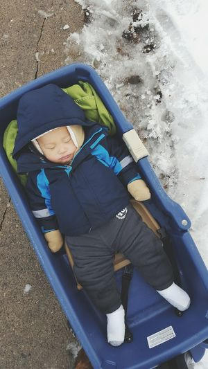 High Angle View Of Toddler Sleeping In Baby Carriage On Footpath