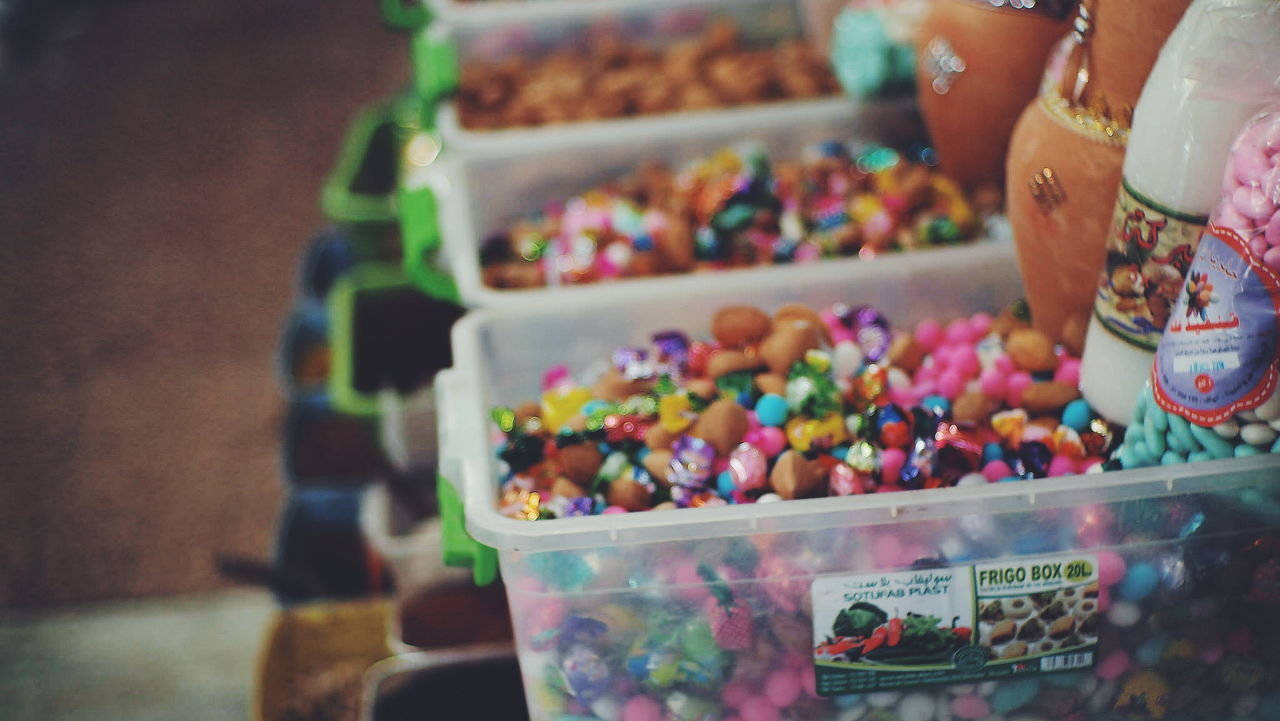 food and drink, sweet food, multi colored, food, container, sweet, variation, choice, for sale, retail, candy, selective focus, one person, large group of objects, indoors, human body part, indulgence, store, abundance, freshness, temptation, hand, retail display