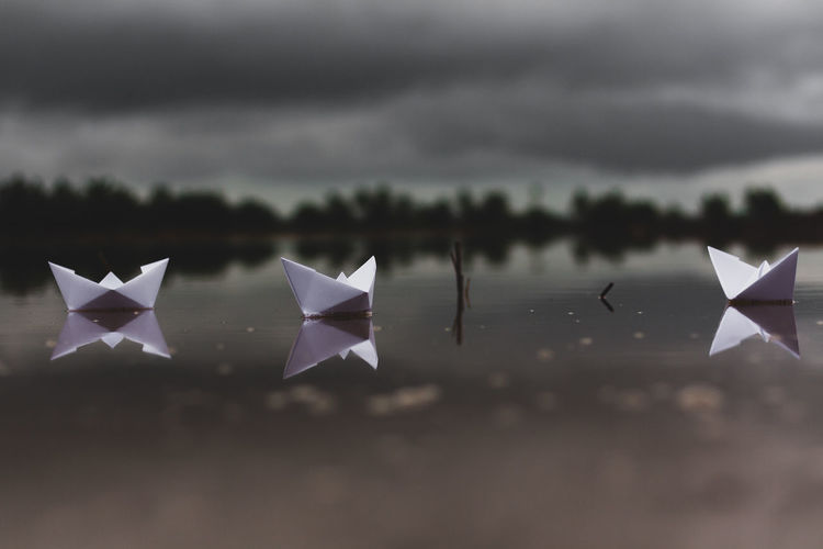 Paper boats in lake against cloudy sky