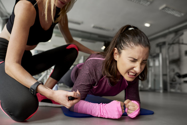 Instructor assisting woman in exercising at gym
