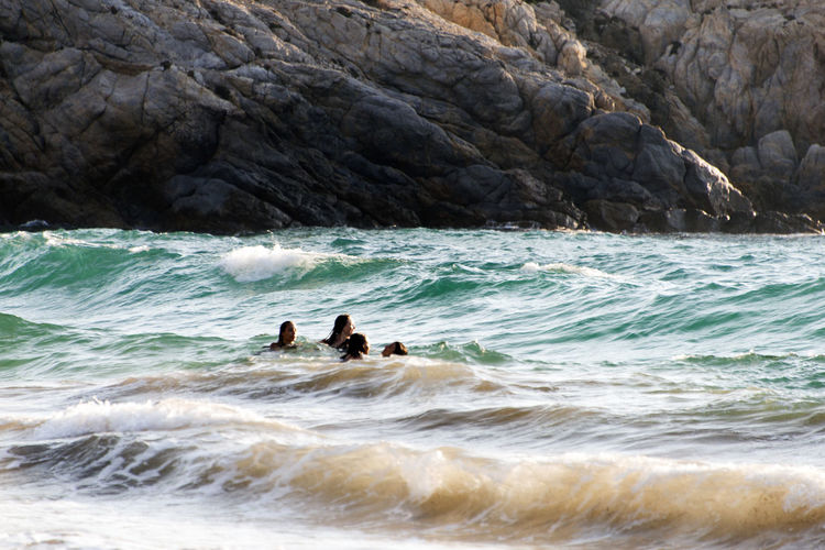 People playing, swimming in the waves in the island of Patmos, Greece in summer time Adventure Aquatic Sport Beauty In Nature Day Land Leisure Activity Lifestyles Men Motion Nature Outdoors People Real People Scenics - Nature Sea Sport Surfing Two People Water Wave