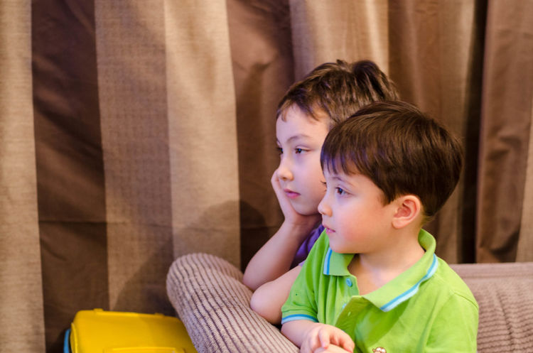 Young brothers sat together watching television. Bonding Boys Brothers Brown Curtains Child Childhood Evening Indoors  Sat Sat Down Sitting Sitting Togetherness Two People Watching Television Watching Tv Young