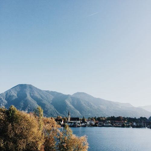 Tegernsee town amidst lake and mountains against clear sky