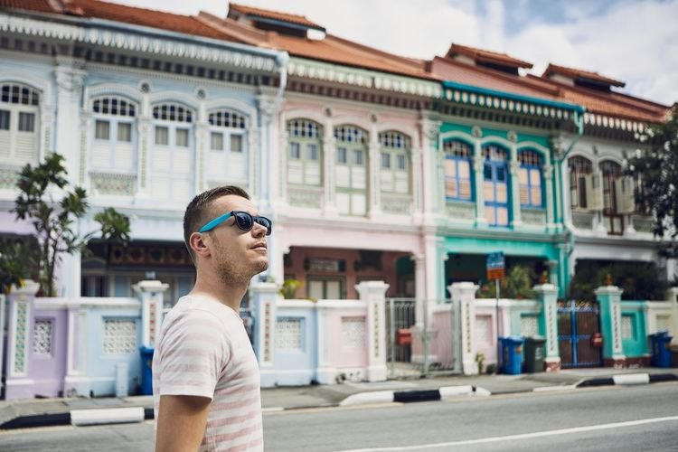 Man wearing sunglasses while standing on street in city