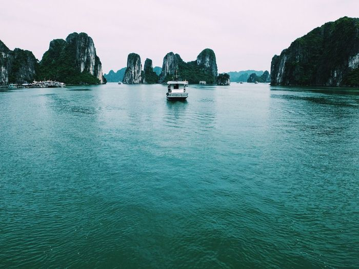 Boat In Sea Against Rock Formations At Halong Bay