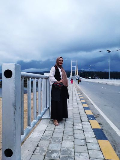 Full length of woman standing on railing against sky
