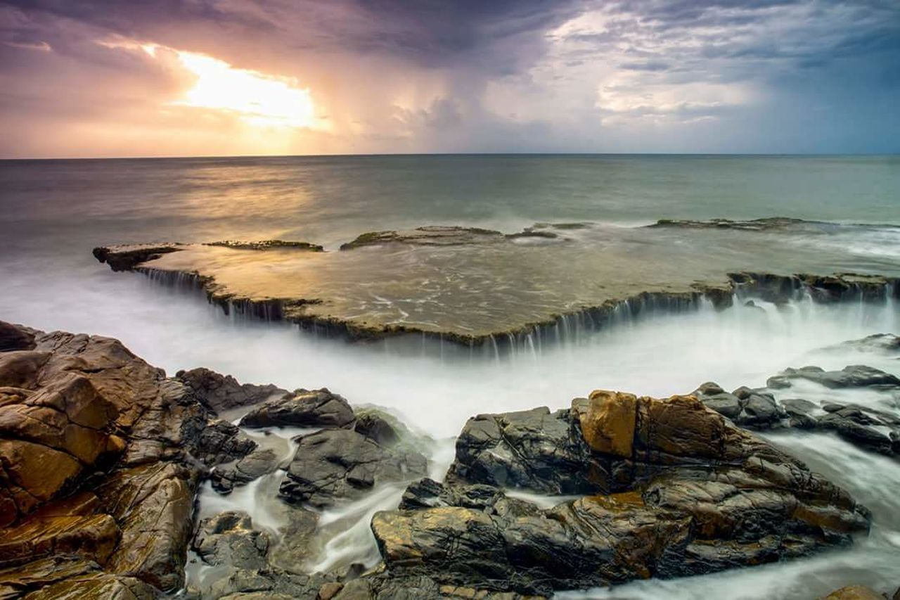 beauty in nature, sea, cloud - sky, water, scenics, nature, sky, horizon over water, sunset, long exposure, tranquil scene, dramatic sky, idyllic, motion, rock - object, outdoors, beach, tranquility, wave, no people, power in nature, travel destinations, day, cliff, waterfall