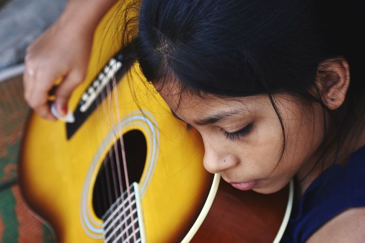 Close-up of girl playing guitar