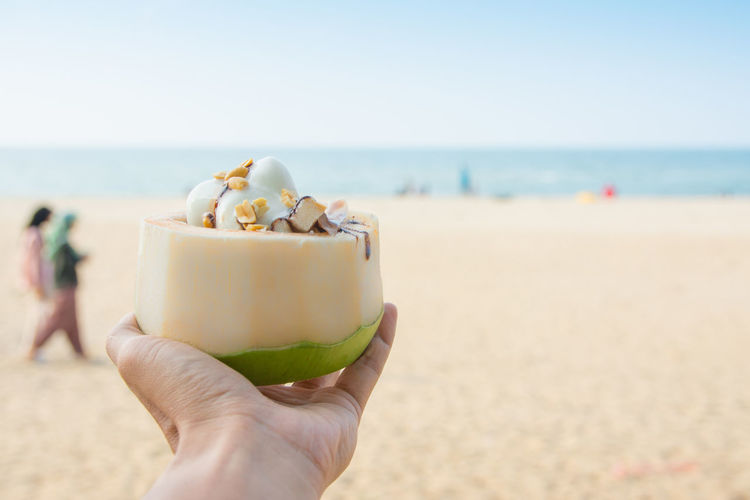 Midsection of person holding ice cream on beach