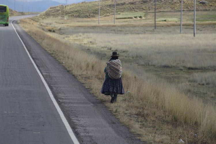 Rear view of woman walking on grassy field by road