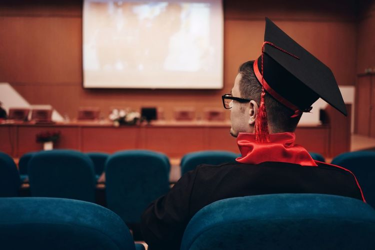 Man Wearing Mortarboard While Sitting In Lecture Hall