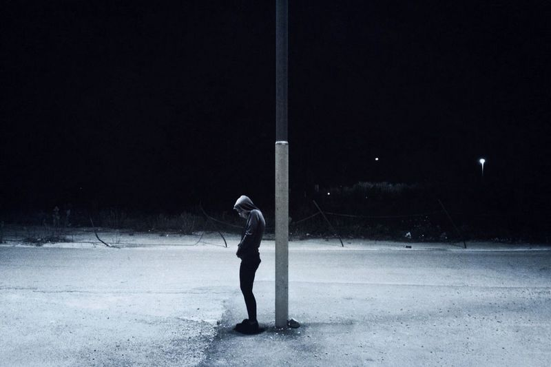 Full length of person standing by pole on snow covered street at night