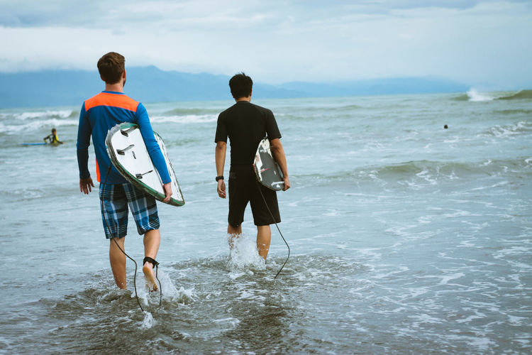 Rear View Of Men Carrying Surfboard While Walking On Shore
