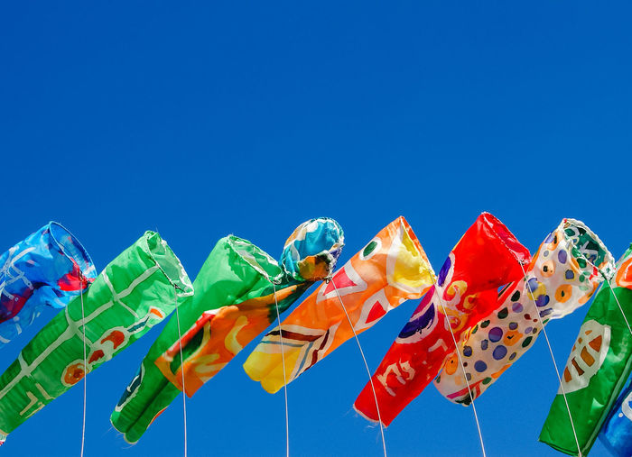Close-up of multi colored windsocks against clear sky