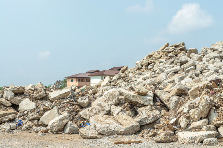 Low angle view of rocks and buildings against sky