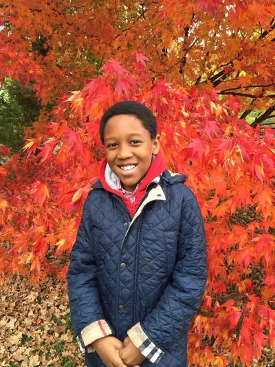 Portrait Of Smiling Boy Standing Against Maple Trees During Autumn