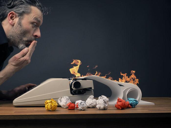 Man Looking At Burning Typewriter Against Wall