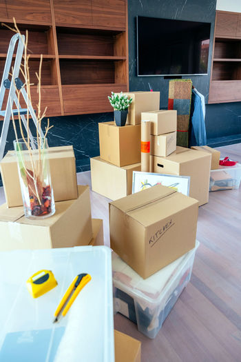 Large living room with stack of moving boxes Architecture Box Decor Modern Moving Apartment Boxes Cutter Design Empty Estate Furniture Home Interior House Living Room Luxury Meter Move New Home Nobody Relocation Space Spacious Style Vertical