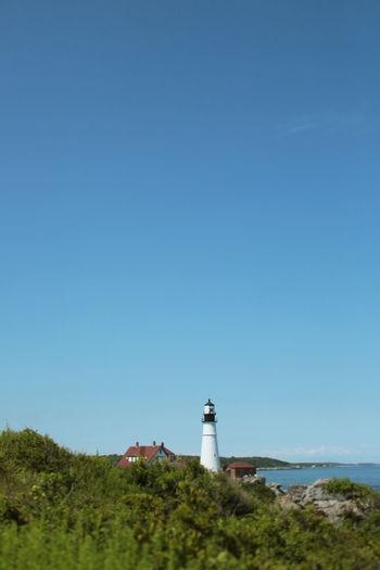 Lighthouse by building against clear blue sky