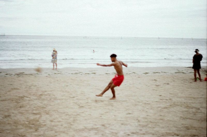 Beach Sea Water Horizon Horizon Over Water Sky Sand Shirtless Outdoors Day Full Length Men Red Color Red Sandy Beach Beach Football Football Action Action Shot  France
